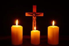 Crucifix et trois bougies brûlantes dans l'obscurité Priez à Jesu Photographie stock