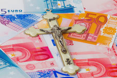 Crucifix on euro banknotes Stock Photography
