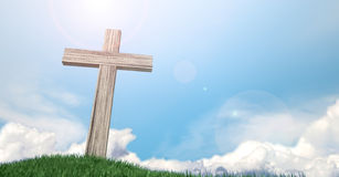 Crucifix On A Grassy Hill And Blue Sky. A wooden crucifix on top of a green grassy hill on a warm sunny blue sky  background with white fluffy clouds Stock Images