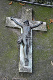 Crucifix on grave. Crucified on ancient tomb and forgotten by all Stock Photo