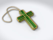 Crucifix isolated on white with pendant. Sapphire green precious stone crucifix in golden wire, isolated on white background, with pendant stock photo