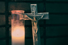 Crucifix and lighted wax candle Royalty Free Stock Photography