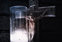 Crucifix and lighted wax candle Royalty Free Stock Image