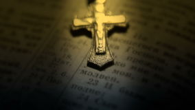 Crucifix lying on open bible pages. Close-up stock video footage