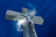 Crucifix with magical light. Jesus Christ on vintage stone cross under blue night sky with mystical haze. Concept of faith, hope, miracle, resurrection royalty free stock photography