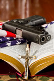 Protection. Crucifix with an open bible, a gun and an american flag in the background with a shallow depth of field royalty free stock image