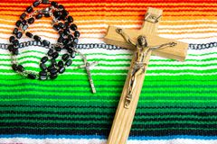 A crucifix and rosary beads on a colorful Mexican sarape. Catholic, religion, christian, Easter concepts royalty free stock image