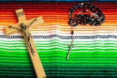 A crucifix and rosary beads on a colorful Mexican sarape stock photo