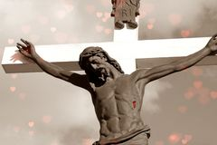 Crucifix in sepia colors with red hearts and wounds on Christ stock photo