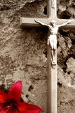 Crucifix in sepia tones on a porous rock with a deep red lily royalty free stock photography
