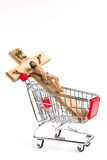 Crucifix in shopping cart. Conceptual representation of commodification of religion, loss of faith, blasphemy Royalty Free Stock Photo