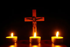 Crucifix and three burning candles in the darkness. Pray to Jesu Stock Image