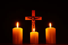 Crucifix and three burning candles in the darkness. Pray to Jesu Stock Photo
