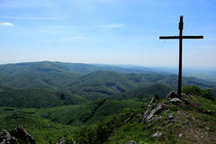 Crucifix on Top of Mountains. Wide View of Forested Hills of Range of Mountain with Big Crucifix on Top Royalty Free Stock Photo