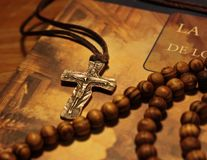 Crucifix and Wooden rosary on religiosos book stock photos