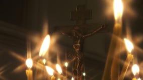 Crucifixión con las velas en un templo religioso ortodoxo almacen de metraje de vídeo