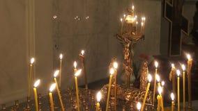 Crucifixión con las velas en un templo religioso ortodoxo metrajes