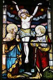 Crucifixion. The Crucifixion of Christ depicted in a Victorian stained glass window over 100 years old. On public display in Saint Mary Magdalene and Saint Denys royalty free stock images