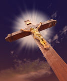 The crucifixion. From a tree with Jesus's gilt figure. Drame sky royalty free stock photo