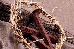 Crucifixion. A crown of thorns and rusty spikes with a rustic aged plank on a brown woven cloth. Used in the Crucifixion of Jesus in Jerusalem. Easter symbols Royalty Free Stock Photography