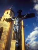 Crucifixion. Crucifixion against the catholic church and blue sky. Western Ukraine Stock Images