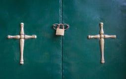 Crucifixion accrochant dans la porte côte à côte Un cadenas scellant les anneaux de l'entrée de passage Peintures se fanant et co Photos stock