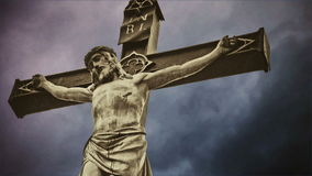 Crucifixion. Christian cross with crucified Jesus Christ statue over dark clouds time lapse. stock video