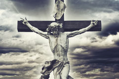 Crucifixion. Christian cross with Jesus Christ statue over storm Royalty Free Stock Photos