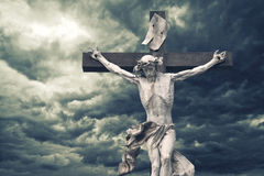 Crucifixion. Christian cross with Jesus Christ statue over storm. Y clouds. religion and spirituality concept Stock Photo