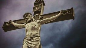 crucifixion A cruz cristã com a estátua crucificada de Jesus Christ sobre a obscuridade nubla-se o lapso de tempo video estoque