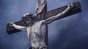 crucifixion A cruz cristã com a estátua crucificada de Jesus Christ sobre a obscuridade nubla-se o lapso de tempo vídeos de arquivo
