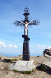 Crucifixion of Jesus against the sky on Mount Petros in Carpathi Stock Images
