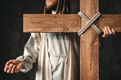 Crucifixion of Jesus Christ, christian religion. Crucifixion of Jesus Christ, symbol of christian religion. Man with cross on black background. The great martyr Stock Photos