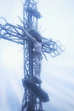 The crucifixion of Jesus Christ statue іn sunrise, snow and fo. Holy cross with crucified Jesus Christ statue іn sunrise, snow and fog Royalty Free Stock Photos