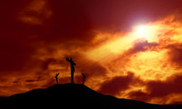 Crucifixion of Jesus With Dramatic Sky and Copy Space. A depiction of the crucifixion of Jesus Christ on a cross with 2 other robbers against a dramatic sunset Royalty Free Stock Images