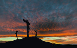 Crucifixion of Jesus With Dramatic Sky and Copy Space. A silhouette of the crucifixion of Jesus Christ on a cross with 2 other robbers against a dramatic sunset Stock Image