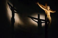 Crucifixo de madeira antigo iluminado dentro de uma igreja italiana histórica com a sombra moldada na parede imagens de stock