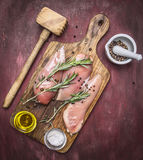 Crude appetizing chicken breast with rosemary, butter and salt on vintage cutting board  hammer for meat Healthy food on woo Royalty Free Stock Photos