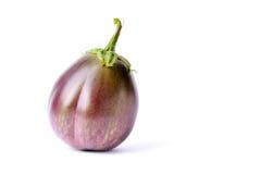 Crude aubergine. One crude aubergine with green stalk on white background Royalty Free Stock Image