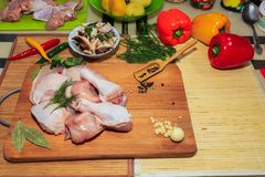 Crude chicken meat on a kitchen table, vegetables and kitchen accessories lie nearby stock images