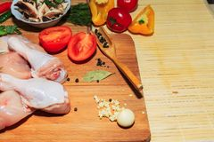 Crude chicken meat on a kitchen table, vegetables and kitchen accessories lie nearby royalty free stock photography
