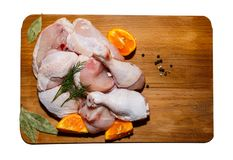 Crude chicken meat on a kitchen table, vegetables and kitchen accessories lie nearby royalty free stock photos