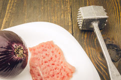 Crude chop and onions on a white plate. Raw chop and hammer on a white plate Royalty Free Stock Images