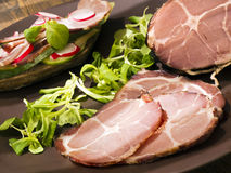 Crude, dried gammon ham with sandwich, salad on plate Royalty Free Stock Photography
