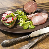 Crude, dried gammon ham with sandwich and salad on plate on wooden table Royalty Free Stock Image