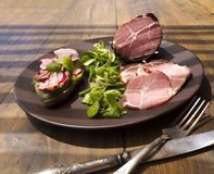 Crude, dried gammon ham with sandwich and salad on plate on wooden table Royalty Free Stock Images