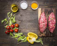 Crude kebab skewers  chopping board vegetables spices wooden rustic background top view close up place text,fr. Crude kebab skewers on a chopping board with Stock Image