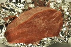 Crude meat in a foil. Piece of crude meat in a foil it is ready to preparation Royalty Free Stock Images