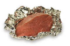 Crude meat in a foil. Piece of crude meat in a foil it is ready to preparation. On a white background Stock Photos