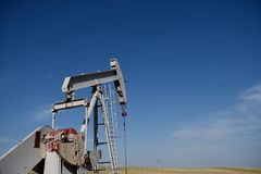 Crude oil production well site pump jack and fields against blue skies in the Niobrara shale. Of Wyoming, USA royalty free stock images